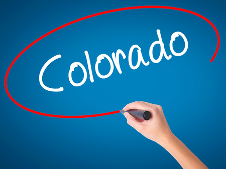 Women Hand writing Colorado  with black marker on visual screen. Isolated on blue. Business, technology, internet concept. Stock Photo