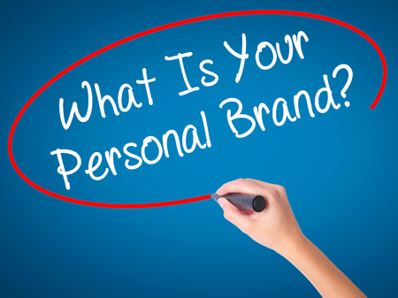 Woman Hand writing What Is Your Personal Brand with black marker on visual screen. Isolated on white. Business, technology, internet concept. Stock Photo