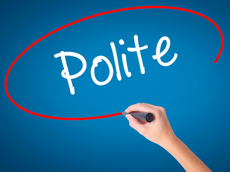polite: Women Hand writing Polite with black marker on visual screen. Isolated on blue. Business, technology, internet concept. Stock Photo