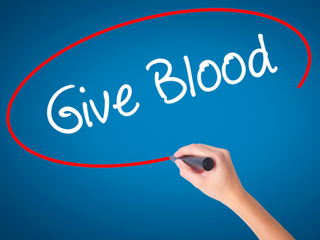 transfused: Women Hand writing Give Blood  with black marker on visual screen. Isolated on blue. Business, technology, internet concept.