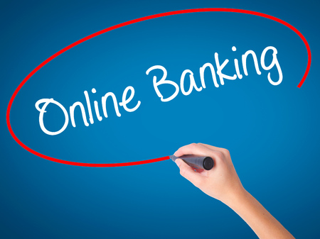 Women Hand writing Online Banking with black marker on visual screen. Isolated on blue. Business, technology, internet concept. Stock Photo