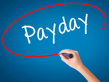Women Hand writing Payday with black marker on visual screen. Isolated on blue. Business, technology, internet concept. Stock Photo