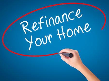 Women Hand writing Refinance Your Home with black marker on visual screen. Isolated on blue. Business, technology, internet concept. Stock Image