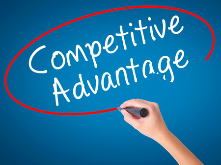 correlate: Women Hand writing Competitive Advantage with black marker on visual screen. Isolated on blue. Business, technology, internet concept. Stock Image Stock Photo
