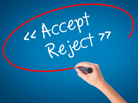 Women Hand writing Accept - Reject  with black marker on visual screen. Isolated on blue. Business, technology, internet concept. Stock Photo
