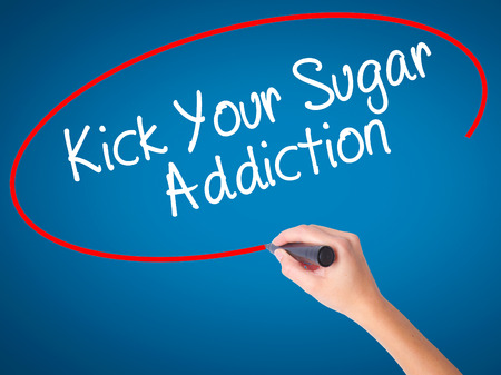Women Hand writing Kick Your Sugar Addiction with black marker on visual screen. Isolated on blue. Business, technology, internet concept. Stock Photo Stock Photo
