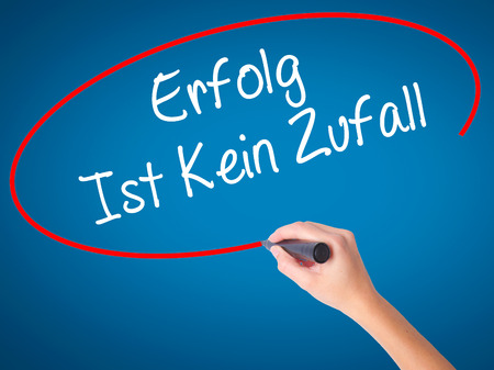 Women Hand writing Erfolg Ist Kein Zaufall (Success Is No Accident in German) with black marker on visual screen. Isolated on blue. Business, technology, internet concept. Stock Photo