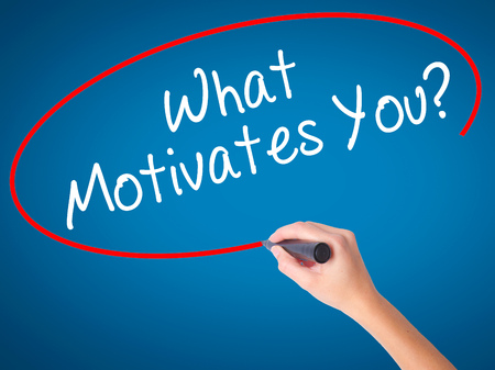 Women Hand Writing What Motivates You? With Black Marker On Visual Screen.  Isolated On  What Motivates You