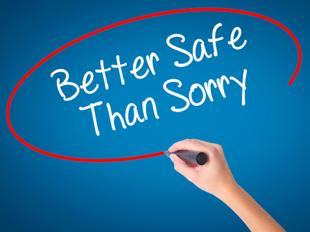 Women Hand writing Better Safe Than Sorry with black marker on visual screen. Isolated on blue. Business, technology, internet concept. Stock Photo