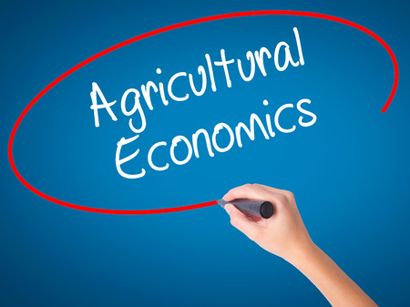 Women Hand writing Agricultural Economics with black marker on visual screen. Isolated on blue. Business, technology, internet concept. Stock Photo