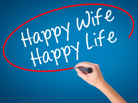 Women Hand writing Happy Wife Happy Life with black marker on visual screen. Isolated on blue. Business, technology, internet concept. Stock Photo
