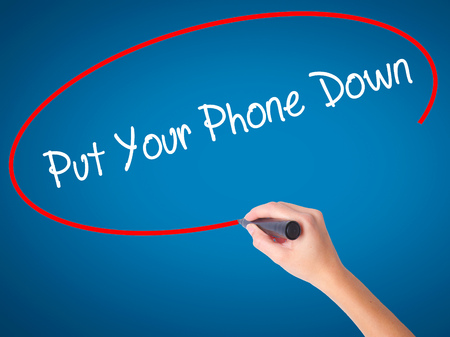 Women Hand writing Put Your Phone Down with black marker on visual screen. Isolated on blue. Business, technology, internet concept. Stock Photo