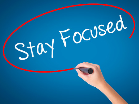 Women Hand writing Stay Focused with black marker on visual screen. Isolated on blue. Business,  technology, internet concept. Stock Photo