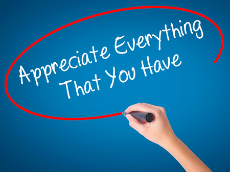 Women Hand writing Appreciate Everything That You Have with black marker on visual screen. Isolated on blue. Business, technology, internet concept. Stock Photo