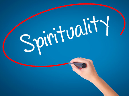 Women Hand writing Spirituality with black marker on visual screen. Isolated on blue. Business, technology, internet concept. Stock Photo