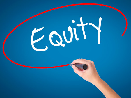 equity: Women Hand writing Equity with black marker on visual screen. Isolated on blue. Business, technology, internet concept. Stock Photo