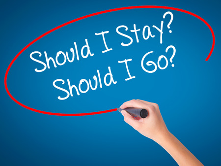 indecisiveness: Women Hand writing Should I Stay? Should I Go? with black marker on visual screen. Isolated on blue. Business, technology, internet concept. Stock Photo