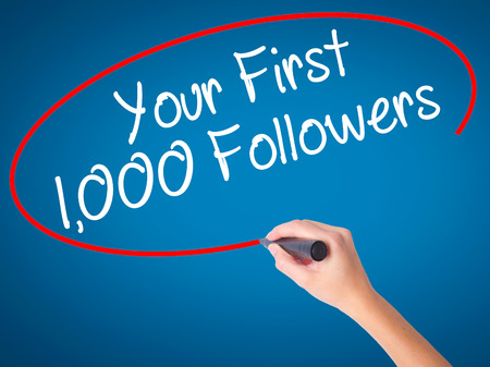 Women Hand writing Your First 1,000 Followers  with black marker on visual screen. Isolated on blue. Business, technology, internet concept. Stock Photo