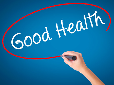 Women Hand writing Good Health with black marker on visual screen. Isolated on blue. Business, technology, internet concept. Stock Image Stock Photo