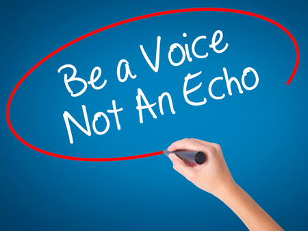 Women Hand writing Be a Voice Not An Echo with black marker on visual screen. Isolated on blue. Business, technology, internet concept. Stock Photo