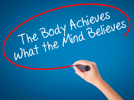believes: Women Hand writing The Body Achieves What the Mind Believes with black marker on visual screen. Isolated on blue. Business, technology, internet concept. Stock Photo