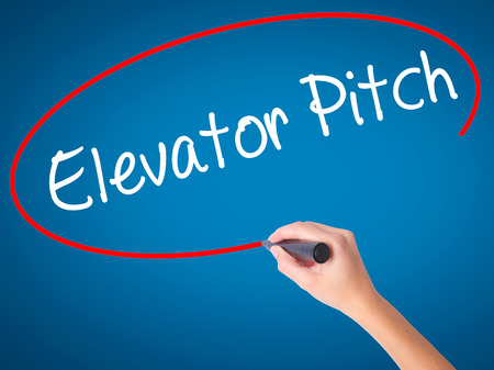 business pitch: Women Hand writing Elevator Pitch with black marker on visual screen. Isolated on blue. Business, technology, internet concept. Stock Photo