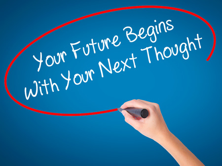 Man Hand writing Your Future Begins With Your Next Thought with black marker on visual screen. Isolated on background. Business, technology, internet concept. Stock Photo Stock Photo