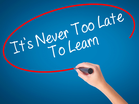 Women Hand writing Its Never Too Late To Learn with black marker on visual screen. Isolated on blue. Business, technology, internet concept. Stock Photo