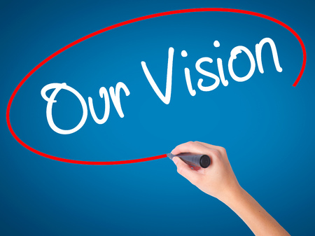 Women Hand writing Our Vision with black marker on visual screen. Isolated on blue. Business, technology, internet concept. Stock Photo