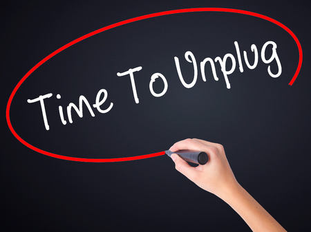 unplugging: Woman Hand Writing Time To Unplug on blank transparent board with a marker isolated over black background. Business concept. Stock Photo
