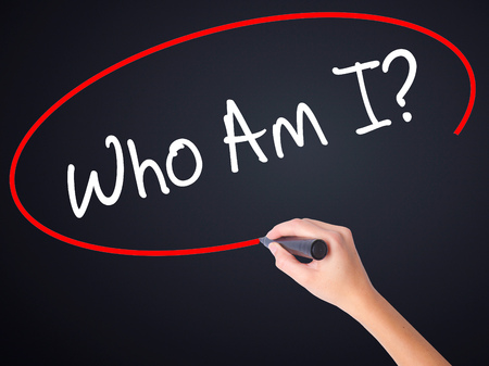 specification: Woman Hand Writing Who Am I? on blank transparent board with a marker isolated over black background. Business concept. Stock Photo