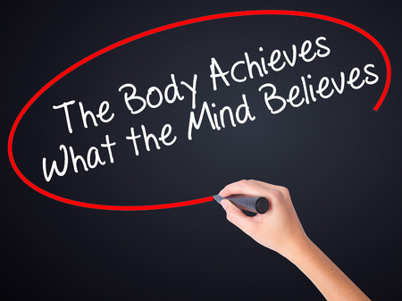 believes: Woman Hand Writing The Body Achieves What the Mind Believes on blank transparent board with a marker isolated over black background. Business concept. Stock Photo