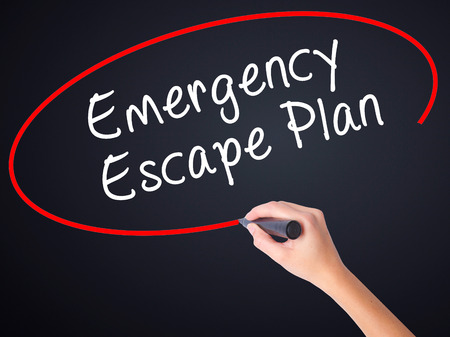 Woman Hand Writing Emergency Escape Plan on blank transparent board with a marker isolated over black background. Business concept. Stock Photo