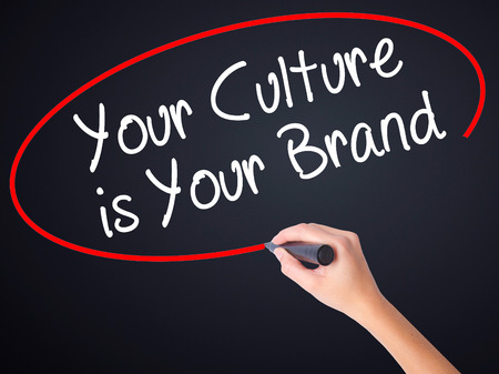 identidad cultural: Woman Hand Writing Your Culture is Your Brand on blank transparent board with a marker isolated over black background. Business concept. Stock Photo