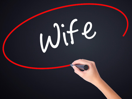 Woman Hand Writing Wife on blank transparent board with a marker isolated over black background. Stock Photo
