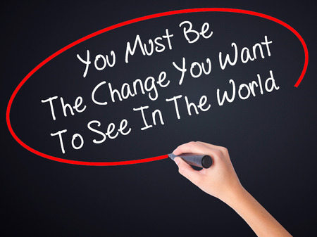 helping others: Woman Hand Writing You Must Be The Change You Want To See In The World on blank transparent board with a marker isolated over black background. Business concept. Stock Photo