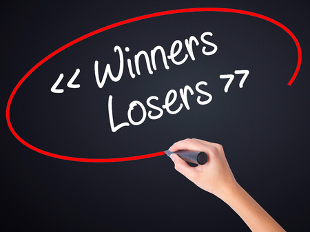 harass: Woman Hand Writing Winners - Losers  on blank transparent board with a marker isolated over black background. Stock Photo Stock Photo