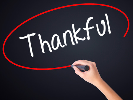 obliged: Woman Hand Writing Thankful  on blank transparent board with a marker isolated over black background. Stock Photo