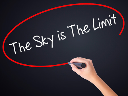 sky is the limit: Woman Hand Writing The Sky is The Limit  on blank transparent board with a marker isolated over black background. Business concept. Stock Photo Stock Photo