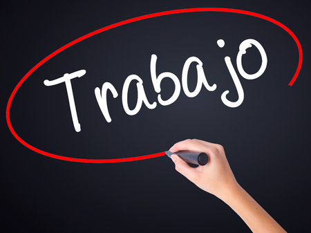 Woman Hand Writing Trabajo  ( work in Spanish) on blank transparent board with a marker isolated over black background. Stock Photo Stock Photo
