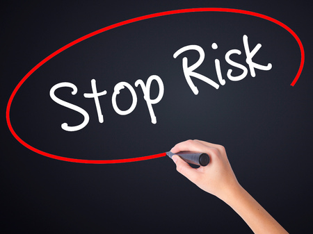 no mistake: Woman Hand Writing Stop Risk on blank transparent board with a marker isolated over black background. Stock Photo