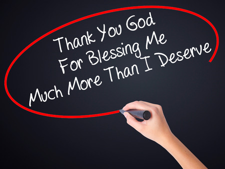 universal love: Woman Hand Writing Thank You God For Blessing Me Much More Than I Deserve on blank transparent board with a marker isolated over black background. Business concept. Stock Photo