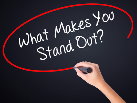 standout: Woman Hand Writing What Makes You Stand Out? on blank transparent board with a marker isolated over black background. Stock Photo