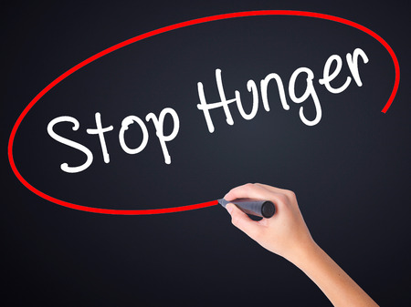 dearth: Woman Hand Writing  Stop Hunger on blank transparent board with a marker isolated over black background. Stock Photo Stock Photo