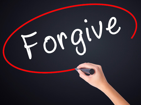regretful: Woman Hand Writing Forgive on blank transparent board with a marker isolated over black background. Business concept. Stock Photo Stock Photo