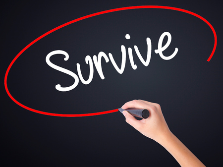 persevere: Woman Hand Writing Survive on blank transparent board with a marker isolated over black background. Stock Photo Stock Photo