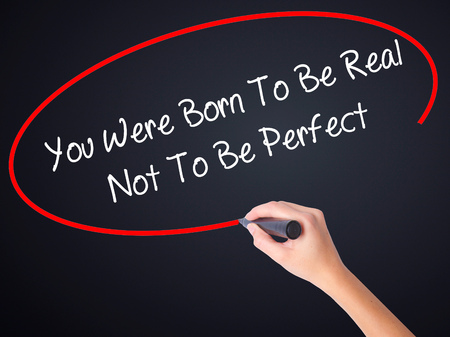 true born: Woman Hand Writing You Were Born To Be Real Not To Be Perfect on blank transparent board with a marker isolated over black background. Business concept. Stock Photo