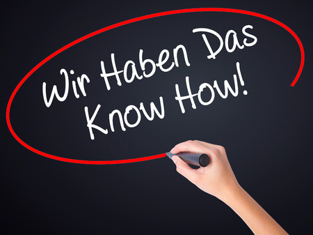 knowhow: Woman Hand Writing Wir Haben Das Know How! (We Have the Know-How in German)  on blank transparent board with a marker isolated over black background. Stock Photo
