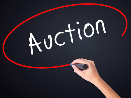vend: Woman Hand Writing Auction on blank transparent board with a marker isolated over black background. Business concept. Stock Photo