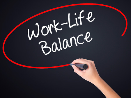 health equity: Woman Hand Writing Work-Life Balance on blank transparent board with a marker isolated over black background. Business concept. Stock Photo Stock Photo